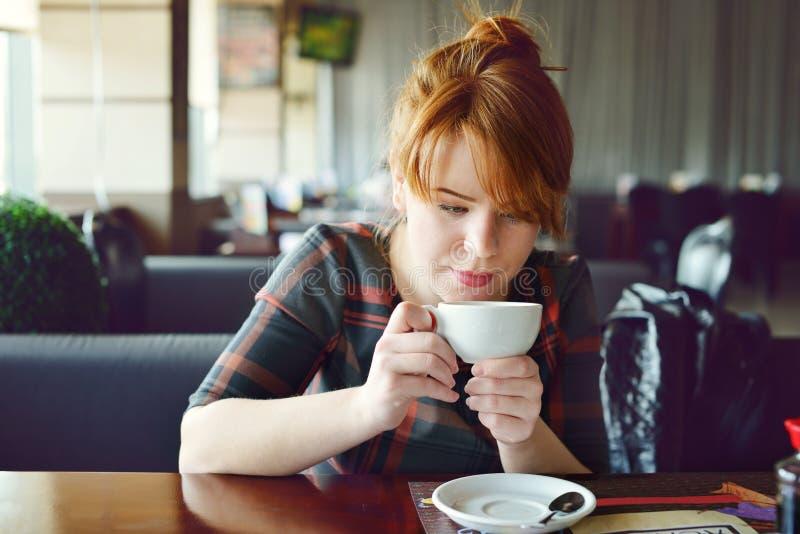 Ładna rudzielec młoda kobieta w kawiarni zdjęcie royalty free