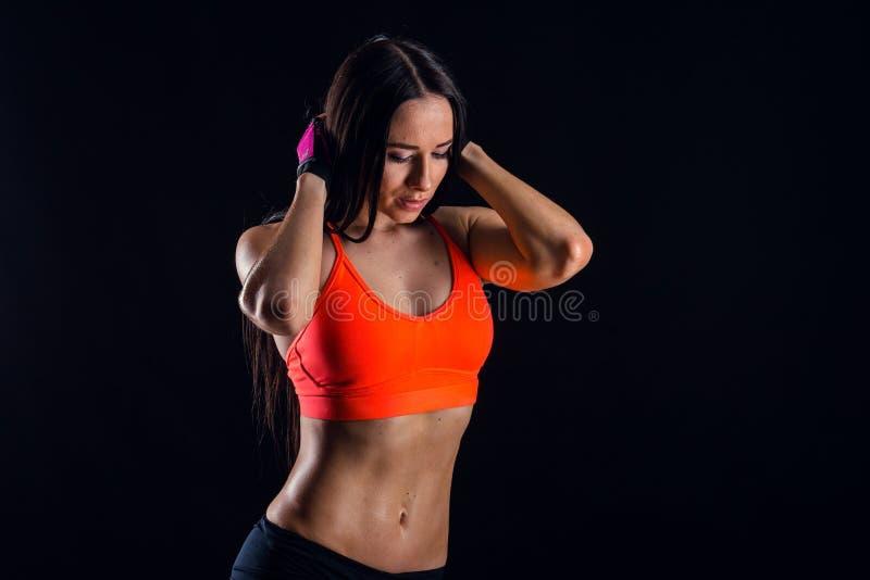 Ładna seksowna sprawności fizycznej kobieta pokazuje brzusznych mięśnie odizolowywających nad czarnym tłem Wyszkolony żeński ciał zdjęcie royalty free