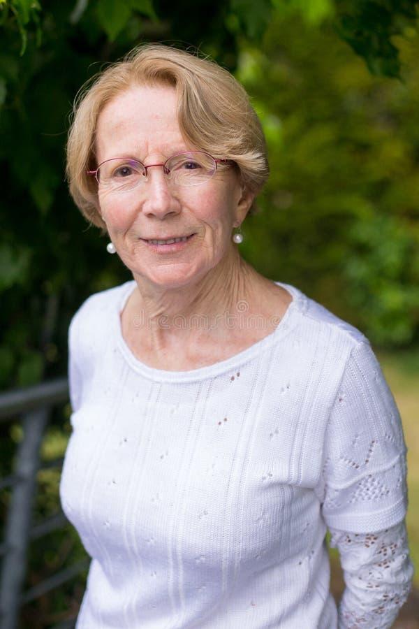 Ładna starsza kobieta jest uśmiechnięta przy kamerą w pięknym ogródzie obraz stock