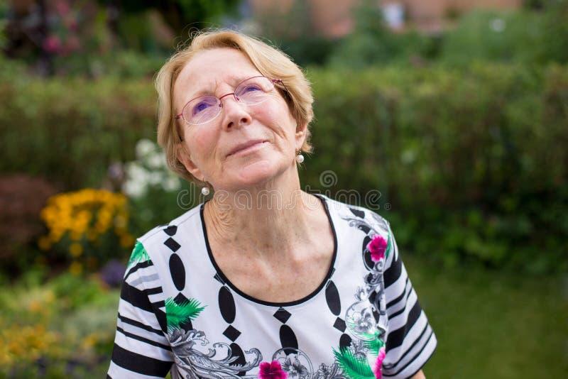 Ładna starsza kobieta marzy w pięknym ogródzie zdjęcia stock