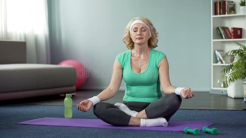 Ładna starsza kobieta medytuje w lotosowej pozie, aktywny styl życia, opieka zdrowotna obraz stock