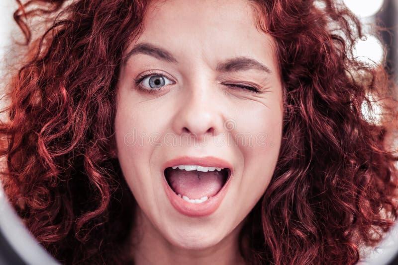 Ładna szczęśliwa czerwona z włosami kobieta mruga ty fotografia royalty free