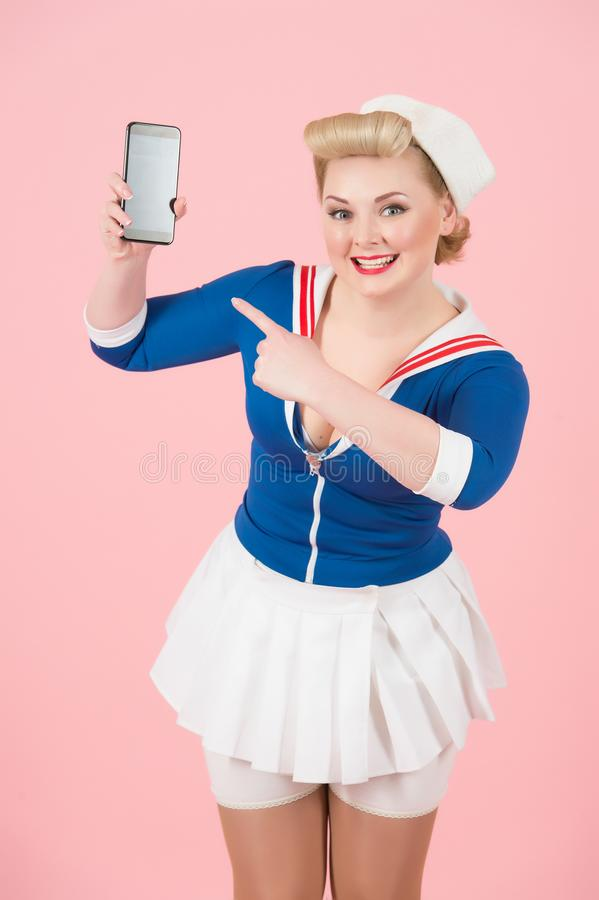 Ładna szpilka projektował dziewczyna szczęśliwego wskazuje telefon z wiadomością Szpilka styl z nowożytnymi urządzeniami łącznośc fotografia stock