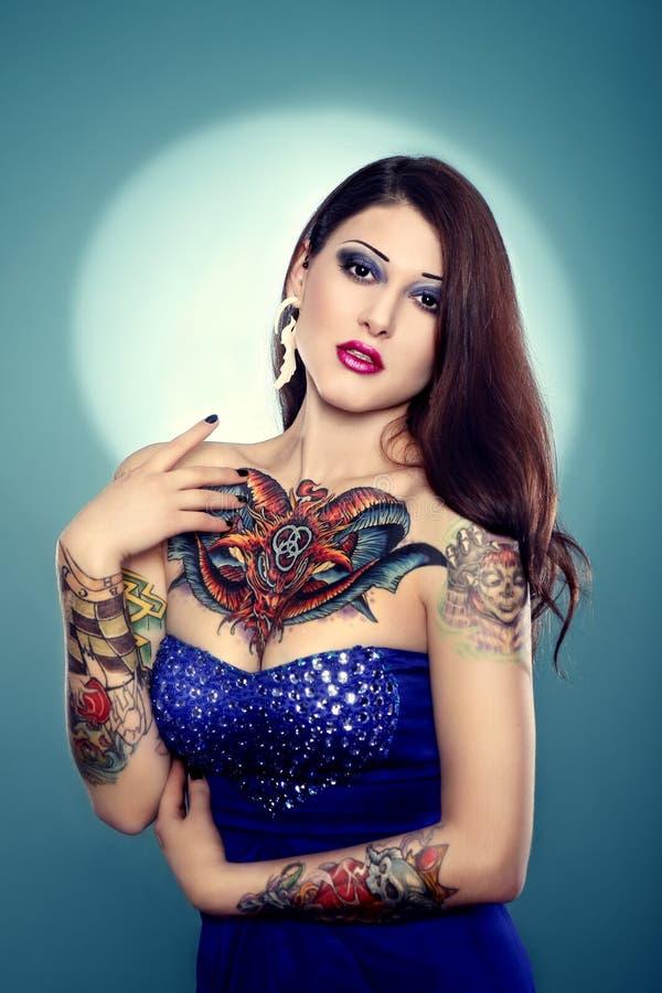 Ładna tatuująca dziewczyna w zmroku - błękit suknia obrazy royalty free
