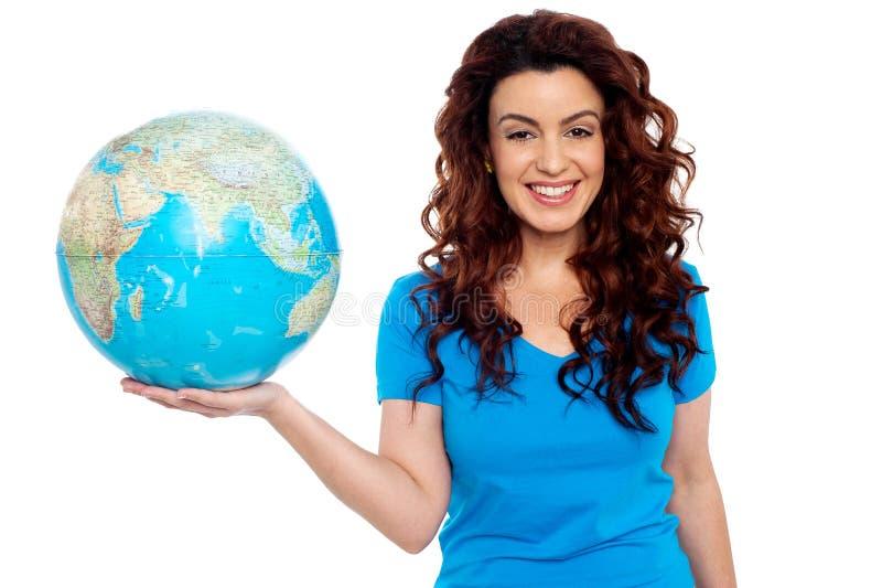 Ładna uśmiechnięta dziewczyny mienia kula ziemska w prawej ręce zdjęcie royalty free