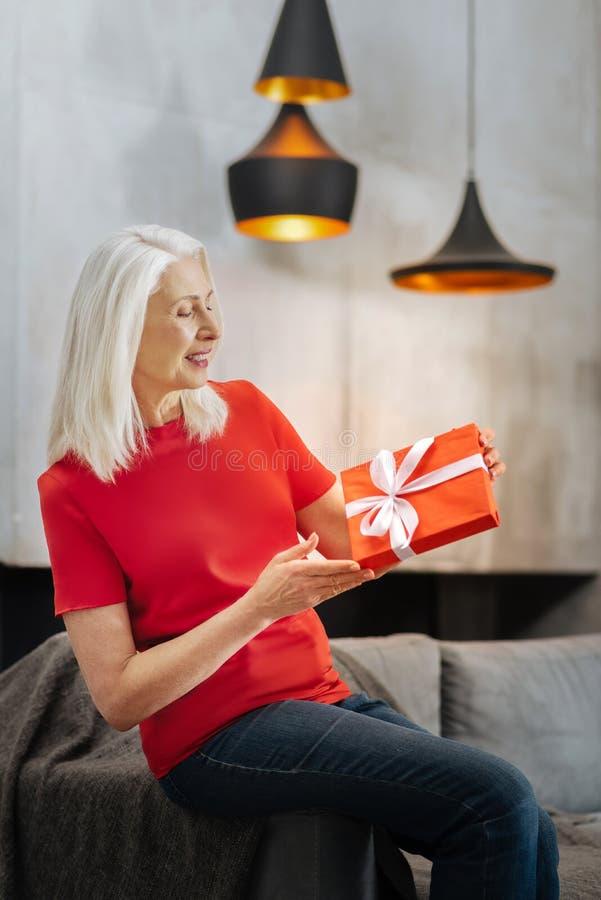 Ładna zadowolona kobieta patrzeje jej prezent obraz royalty free