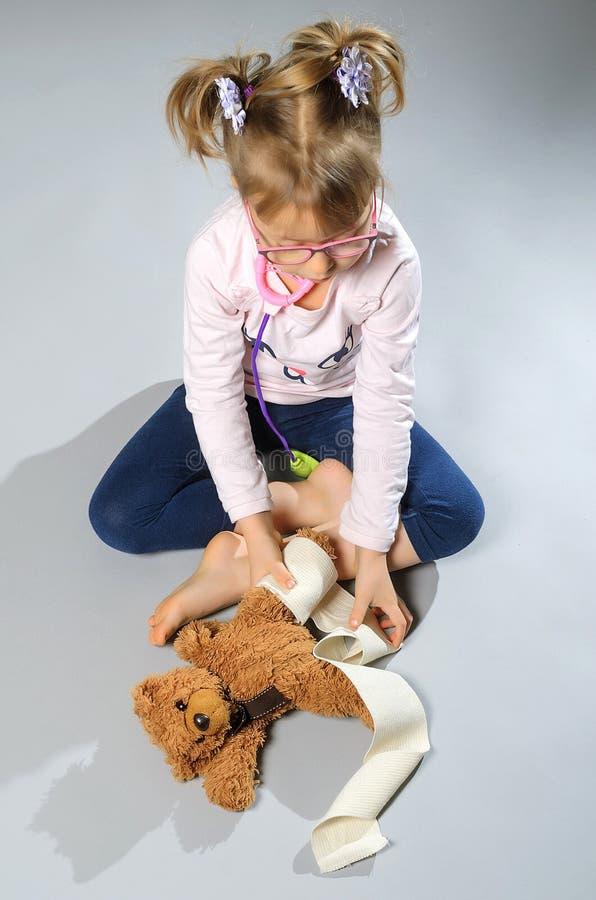 Ładne dziewczyn sztuki w lekarce taktują misia na szarzy półdupki zdjęcie stock