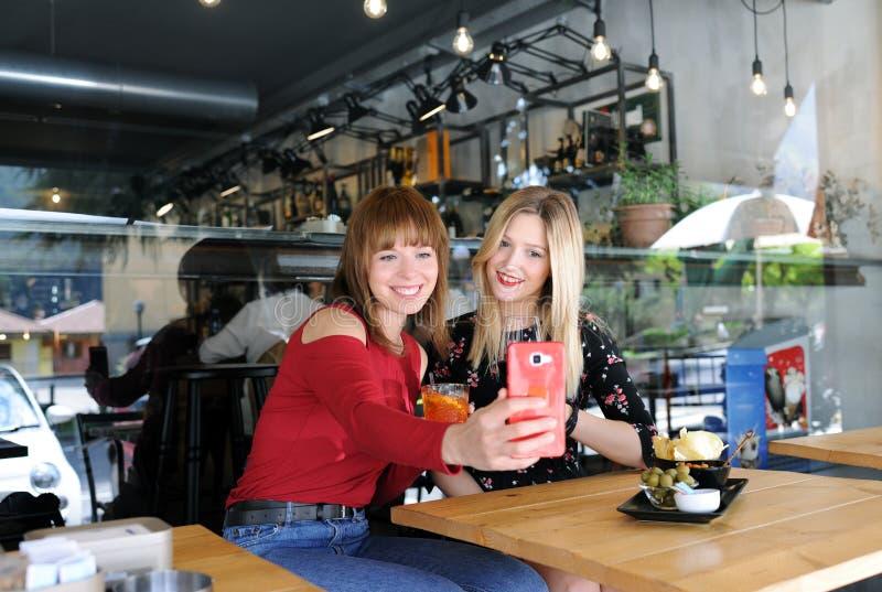 Ładne dziewczyny bierze selfie w kawiarni zdjęcie stock
