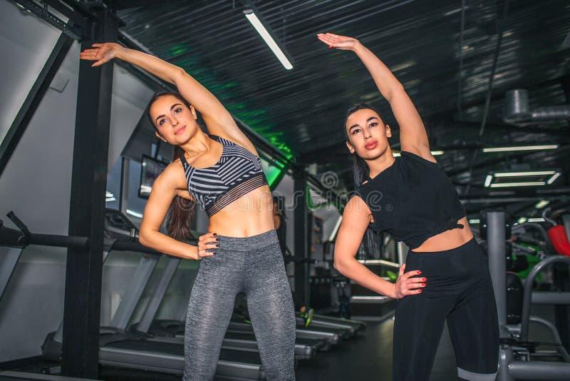 Ładne i ufne młode kobiety rozciąga w gym Stoją wpólnie i opierają popierać kogoś Modele patrzeją przednimi jeden i utrzymanie zdjęcie stock