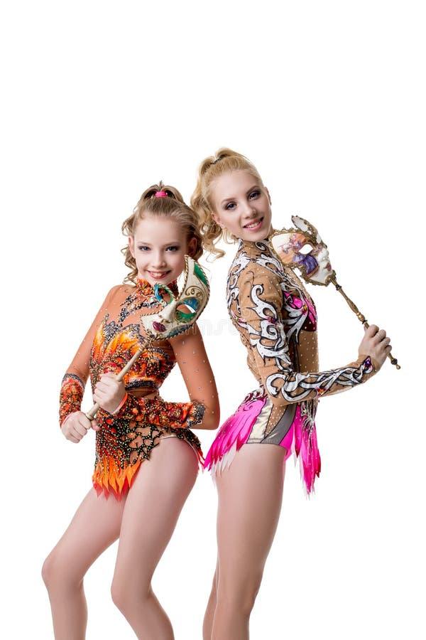 Ładne młode gimnastyczki pozuje z karnawałowymi maskami obraz stock