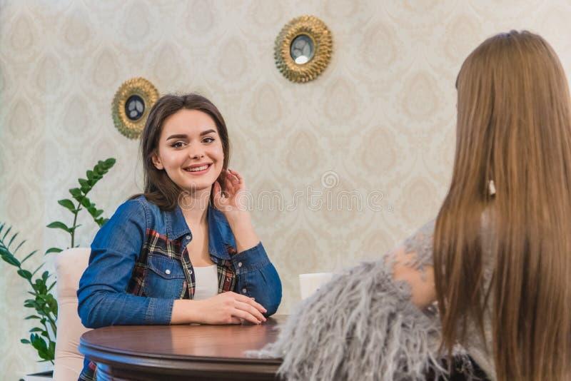 Ładne młode kobiety siedzi w kawiarni Piękny i ciepły strzał Kaukaska dziewczyna w przypadkowej odzieży przez okno fotografia stock