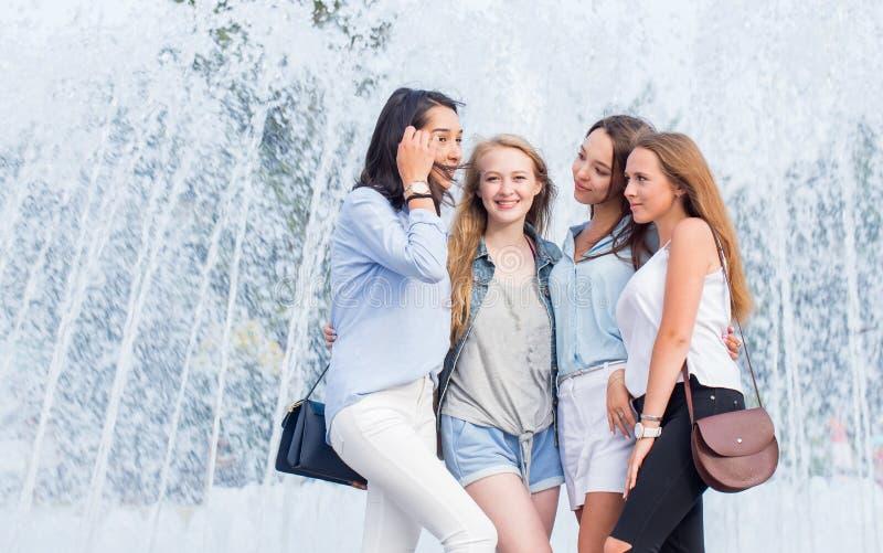 Ładne studenckie dziewczyny ma zabawę outdoors Grupa atrakcyjne rozochocone kobiety opowiada blisko fontanny w mieście fotografia stock