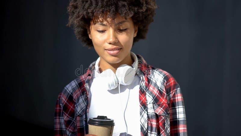 Ładnego amerykanina żeńskiego mienia herbaciana filiżanka plenerowa, będący ubranym hełmofon, młodość obraz royalty free