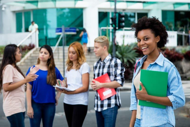 Ładnego amerykanina afrykańskiego pochodzenia żeński uczeń z grupą zawody międzynarodowi obraz stock