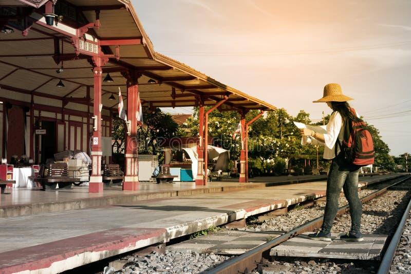 Ładnego Azjatyckiego podróżnika backpacker żeńska przyglądająca mapa przy stacją kolejową obraz stock