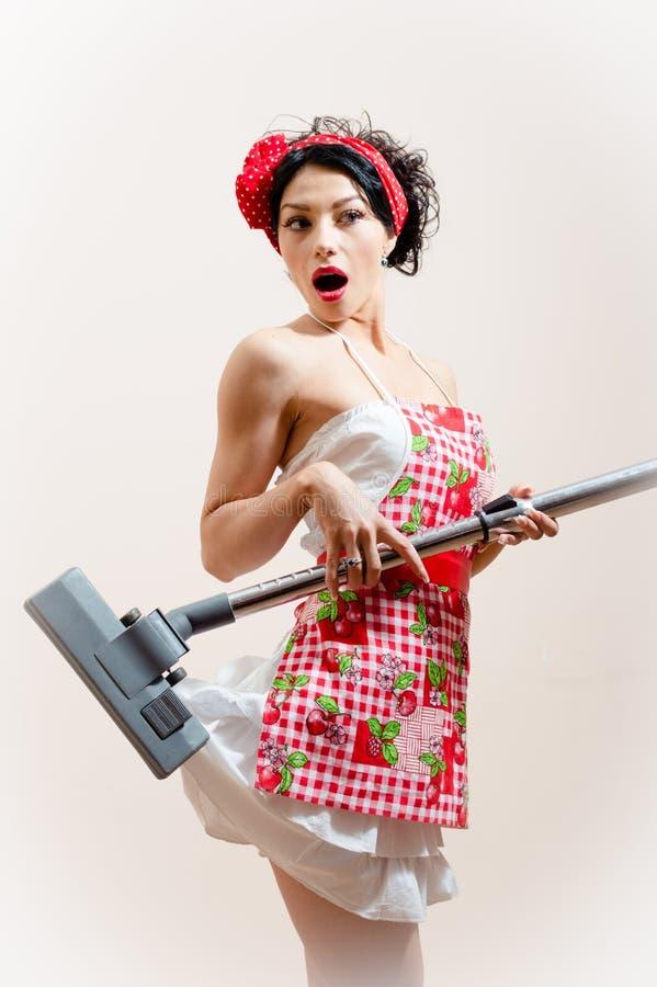 Ładnego housewifу młodej kobiety szpilki atrakcyjna seksualnie śmieszna dziewczyna zaskakuje ponieważ próżniowy cleaner je jej s obrazy royalty free