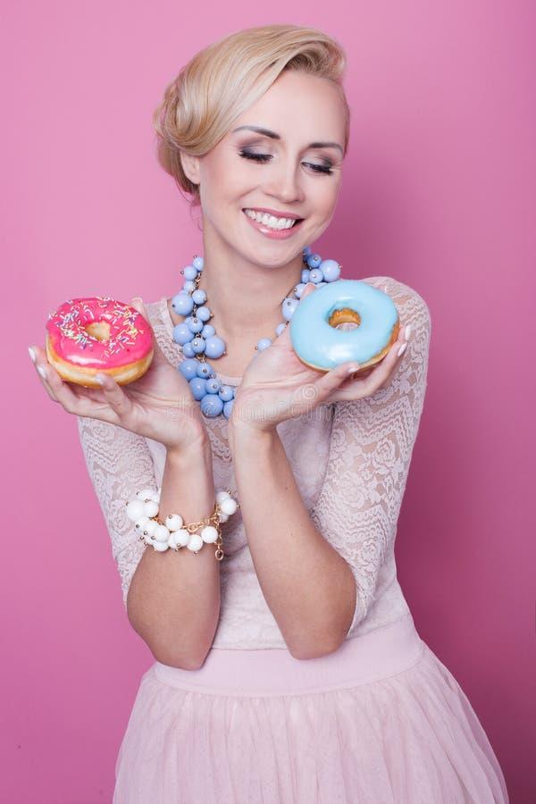 Ładnego młoda kobieta chwyta kolorowi donuts kolorów strzałek głębii pola płycizny miękka część zdjęcia stock