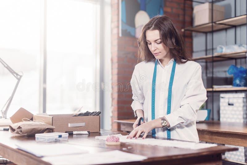 Ładnego młodego projektanta mody tnący płótno używać nożyce w studiu podczas gdy pracujący obraz royalty free