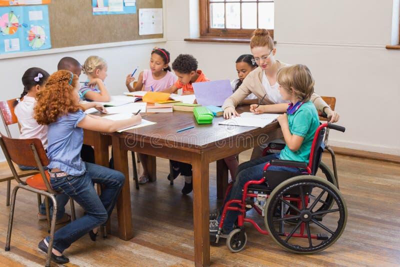 Ładnego nauczyciela pomaga ucznie w sala lekcyjnej zdjęcia royalty free