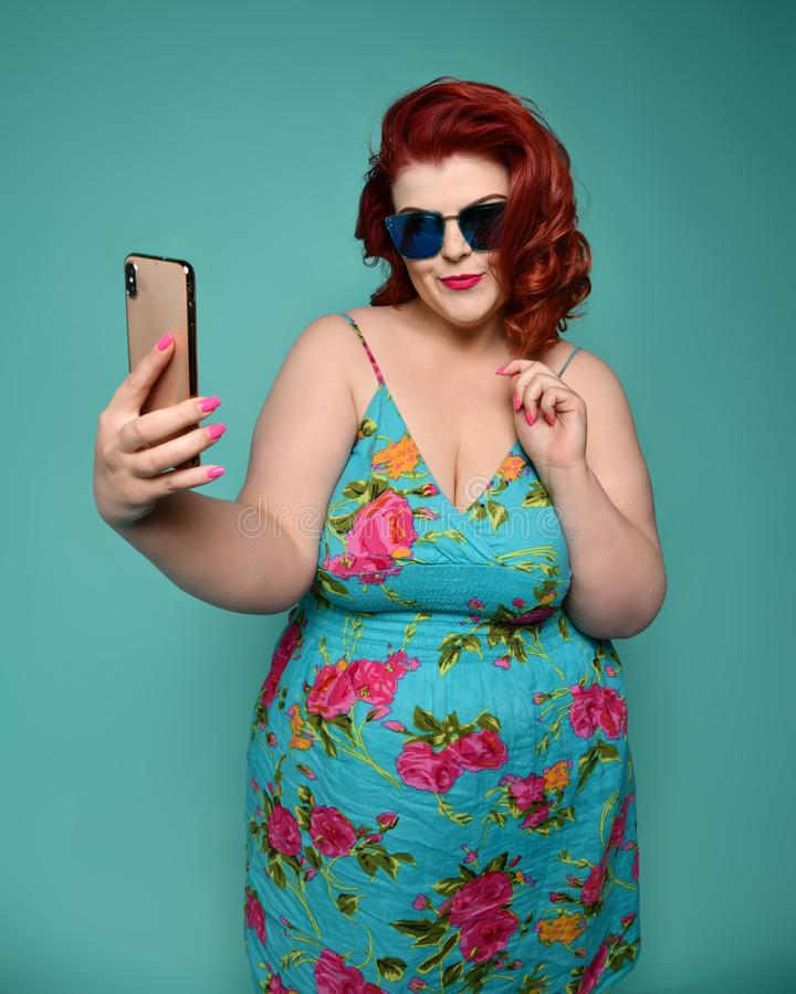 ?adnego rozmiaru gruba kobieta w moda okularach przeciws?onecznych i kolorowych ubraniach fasonuje selfie jakby jest ?adnym i nie obrazy stock