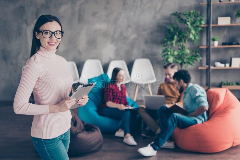 Ładnej atrakcyjnej rozochoconej damy specjalisty finansisty młodzieżowy mienie w ręki ebook współpracy zarządzania obsiadaniu na  obrazy royalty free