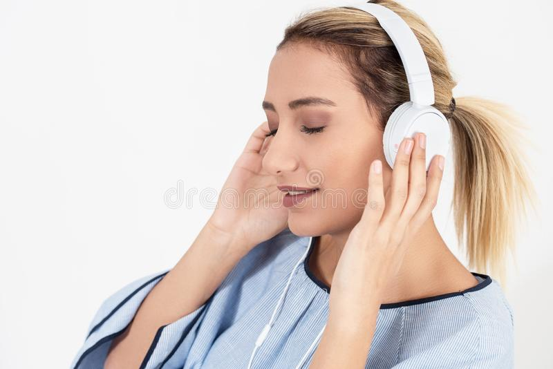 Ładnej dziewczyny słuchająca muzyka z jej hełmofonami na białym tle zdjęcia stock