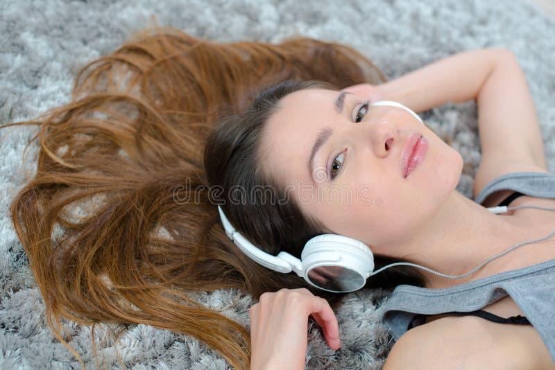 Ładnej kobiety słuchająca muzyka w hełmofonach kłama na podłodze obraz royalty free