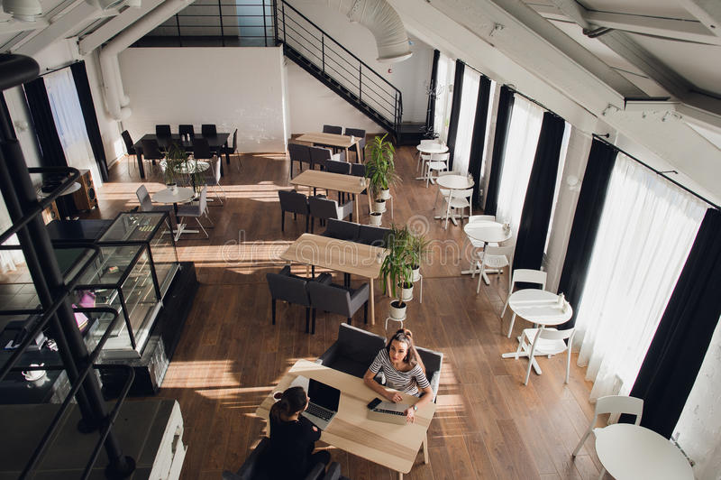 Ładni żeńscy pracownicy cieszą się ich pracę Dwa bizneswomanu siedzą w kawiarni, jeden są przyglądający kamera zdjęcia royalty free