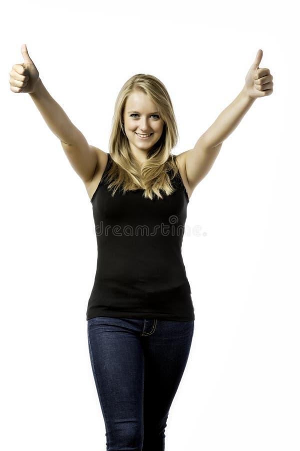 Ładni blond dziewczyn helds jej dwa aprobaty zdjęcia stock