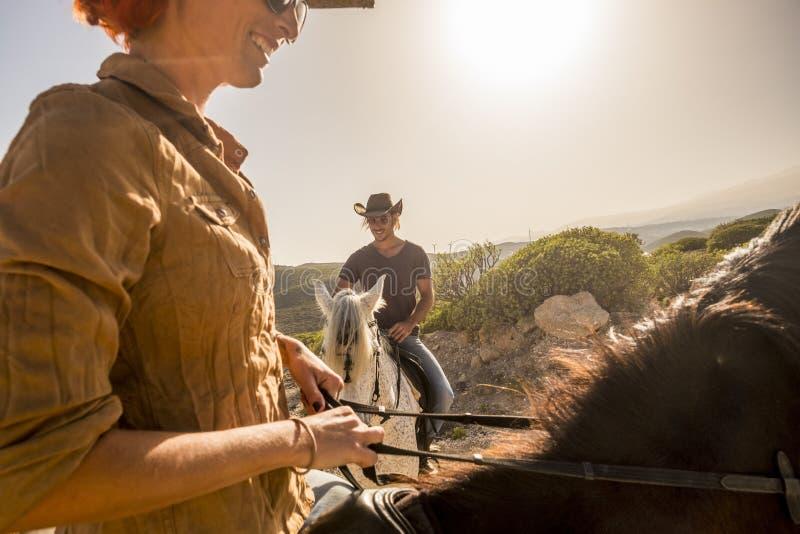 Ładni caucasian kowboje dobierają się przejażdżka konie w wiatrowego ladscape scenicznym miejscu kobieta i mężczyzna wpólnie zaba obraz stock