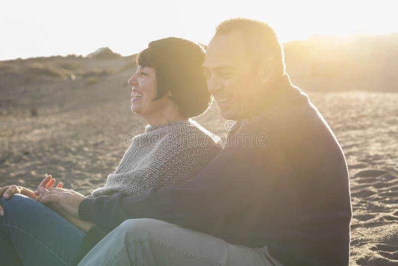 Ładni caucasian ludzie par zabawę, uśmiechy i śmiech wpólnie podczas złotego zmierzchu z backlight na plaży w wakacje zdjęcia royalty free