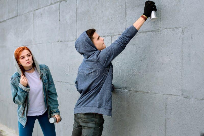 Ładni młodzi nastolatkowie rysuje graffiti Romantyczną datę zdjęcie royalty free