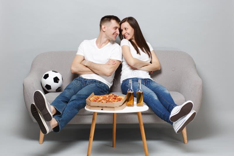 Ładni pary kobiety mężczyzny fan piłki nożnej rozweselają w górę poparcie faworyta drużyny z piłki nożnej piłką, patrzeje each in zdjęcie royalty free