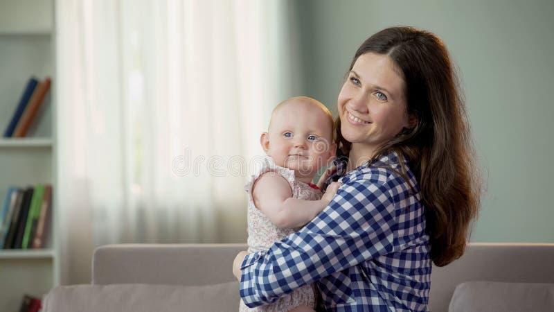 Ładni potomstwa macierzyści, śliczny dziecko córki przytulenie i ono uśmiecha się, szczęśliwa przyszłość obraz royalty free