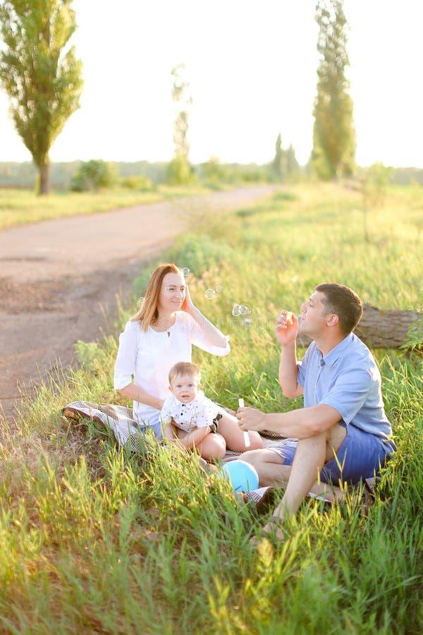 Ładni rodzice siedzi na trawie z małego dziecka i dmuchania bąblami fotografia stock