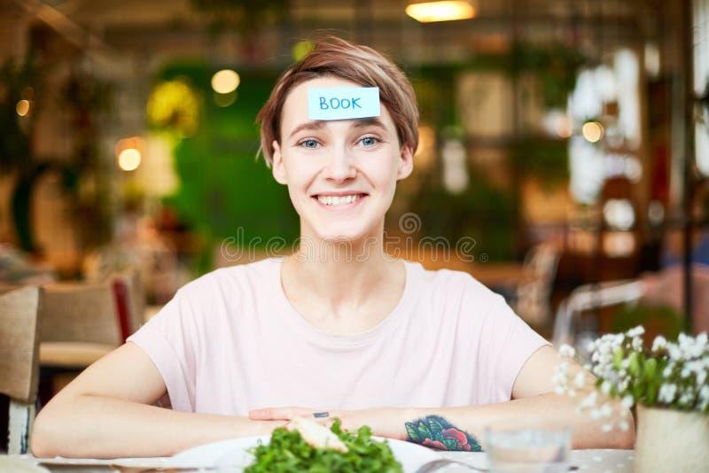 Ładny żeński śmiać się zabawę i mieć w kawiarni obrazy royalty free