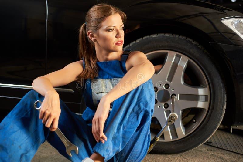 Ładny żeński mechanik siedzi blisko koła czarny samochód obrazy stock