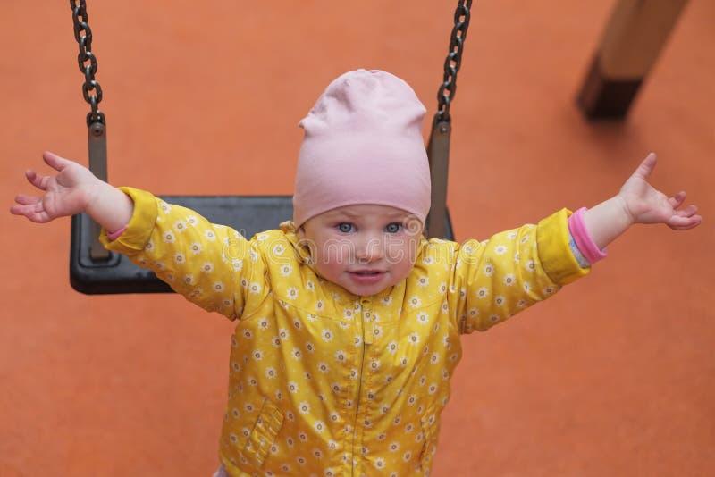 Ładny żeński niemowlak po tym jak huśtać się rozciąga jej rękę zdjęcia stock