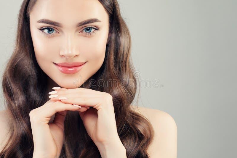 Ładny żeński twarzy zbliżenia portret Jasna skóra, robiący manikiur gwoździe, kędzierzawy włosy i śliczny uśmiech, obraz stock
