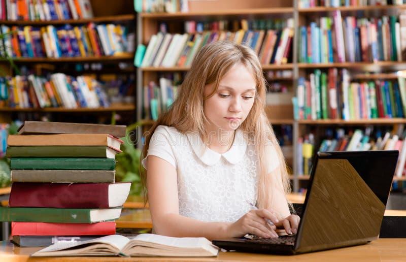 Ładny żeński uczeń pisać na maszynie na notatniku w bibliotece zdjęcie royalty free