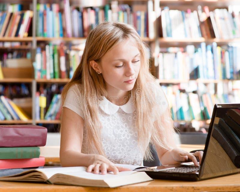 Ładny żeński uczeń pisać na maszynie na notatniku w bibliotece zdjęcie stock