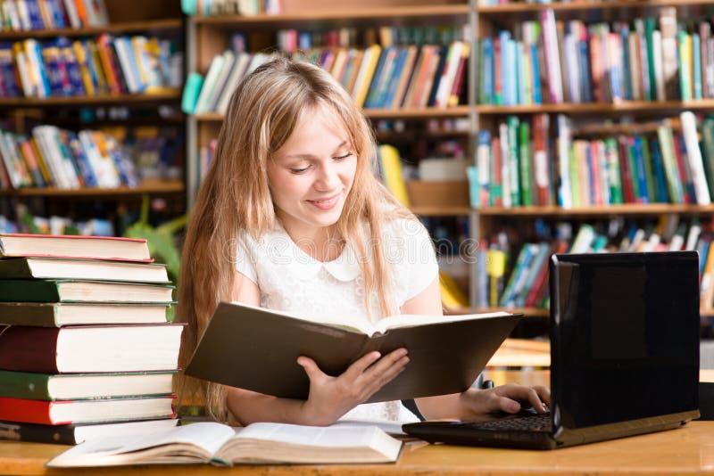 Ładny żeński uczeń pisać na maszynie na notatniku w bibliotece fotografia royalty free