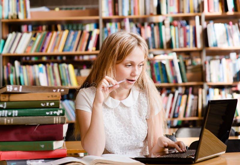 Ładny żeński uczeń używa laptop w bibliotece zdjęcia stock