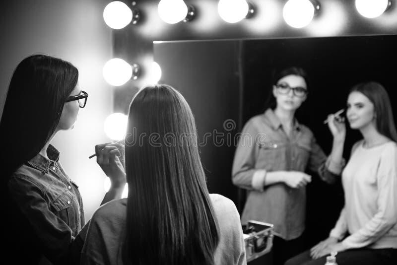 Ładny atrakcyjny makeup artysta patrzeje w lustro obrazy royalty free