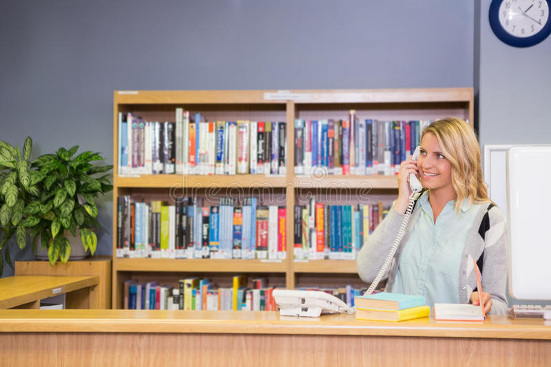 Ładny bibliotekarski działanie w bibliotece obraz stock