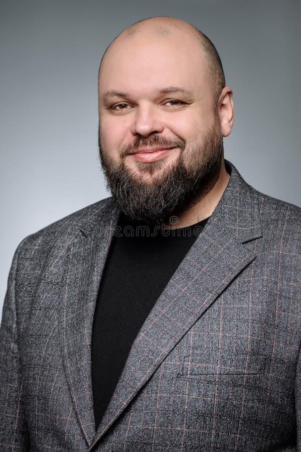 Ładny biznesmen z dobroduszną twarzą jest uśmiechnięty Studio strzał gruby mężczyzna główkowanie przeciw szaremu tłu zdjęcia stock
