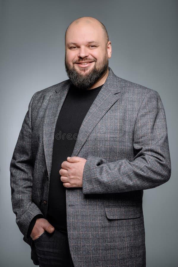 Ładny biznesmen z dobroduszną twarzą jest uśmiechnięty Studio strzał gruby mężczyzna główkowanie przeciw szaremu tłu zdjęcia royalty free