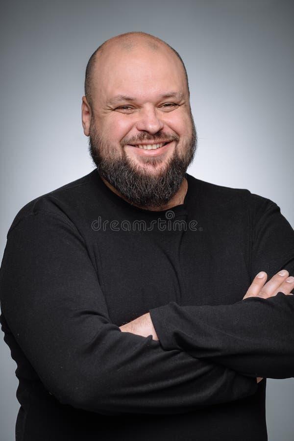 Ładny biznesmen z dobroduszną twarzą jest uśmiechnięty Studio strzał gruby mężczyzna główkowanie przeciw szaremu tłu fotografia stock