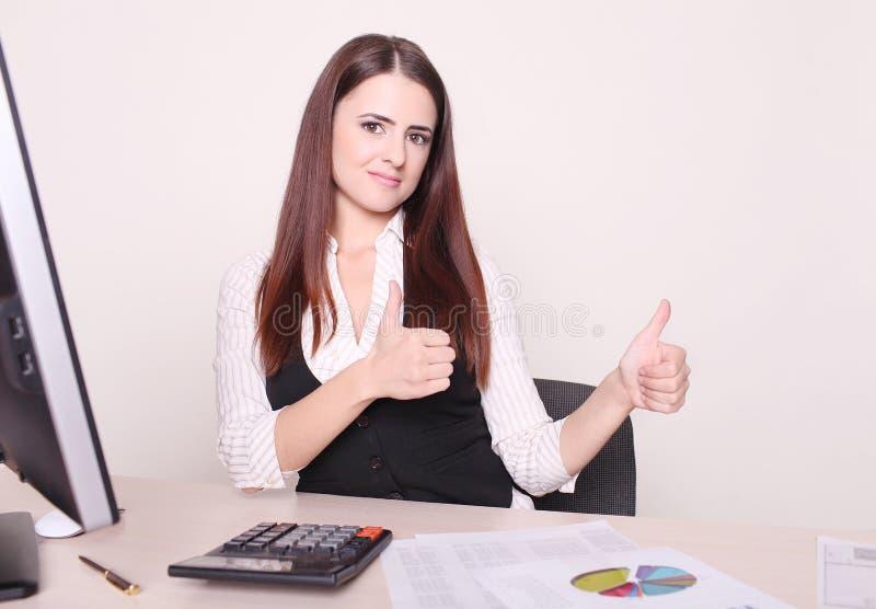 Ładny bizneswoman pokazuje kciuk do kamery przy jej biurkiem w h obraz stock