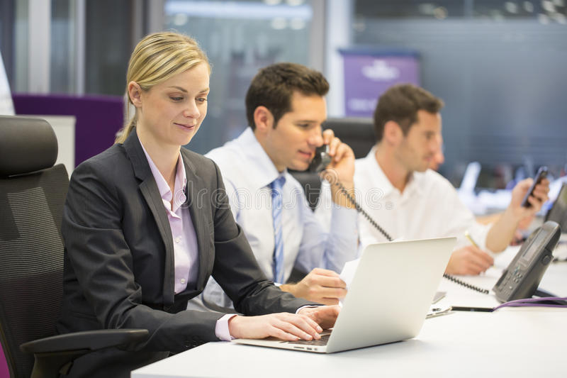 Ładny bizneswoman pracuje na laptopie, biznesmen w backgroun obrazy stock